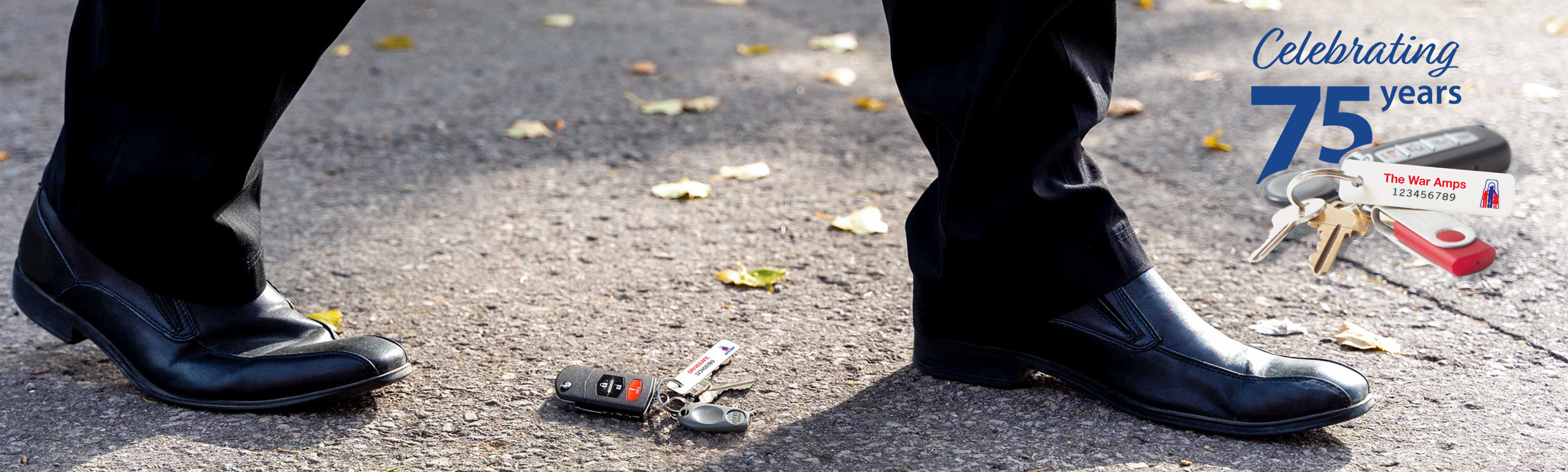 A set of keys with a War Amps key tag attached laying on the ground. Learn more about the Key Tag Service.