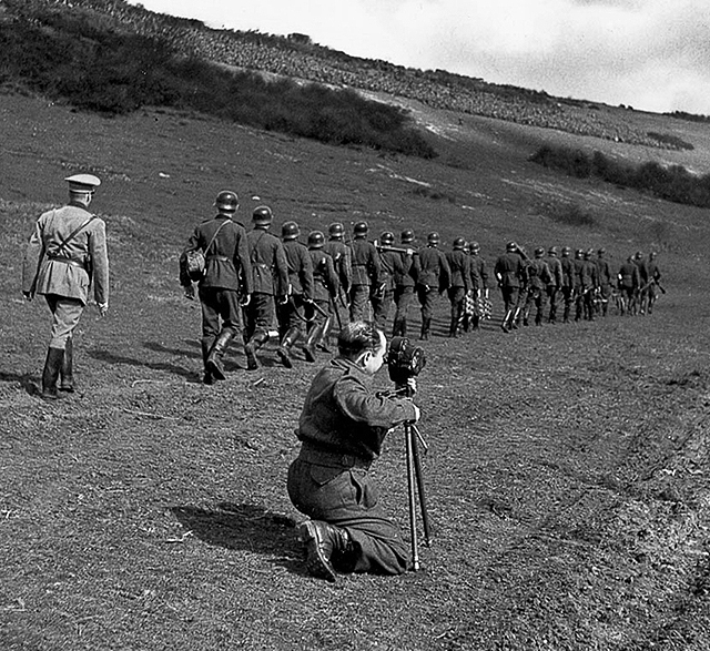Al Grayston takes a picture of troops marching away. Location: Sicily. (Private Collection)