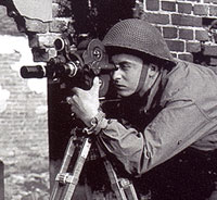 Sgt. G.D. Petty takes Cine pictures of a shelled house. Location: The Netherlands. (LAC PA#136212)