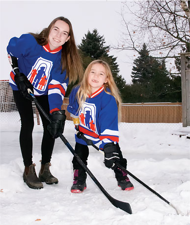 Audrey and Leah standing by an outdoor rink demonstrating how they hold their hockey sticks with their specialized artificial arms.